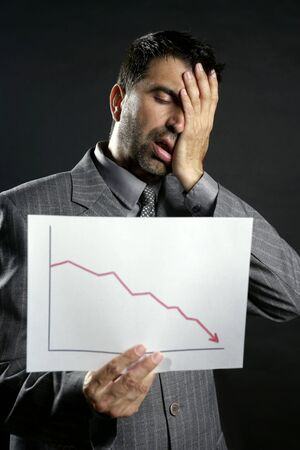 Businessman with bad sales reports chart. Crisis photo