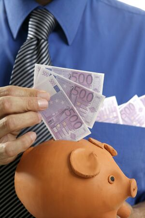 businessman insert euro notes in clay piggy bank photo