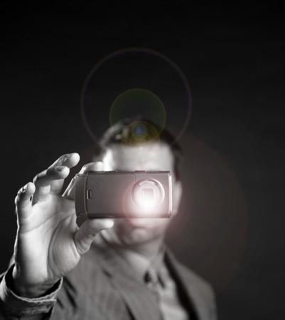 Businessman taking photos, mobile camera, black background Stock Photo - 4097905
