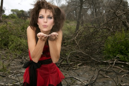 Beautiful woman, black magic on burned forest, red haute couture dress, witch and ashes photo