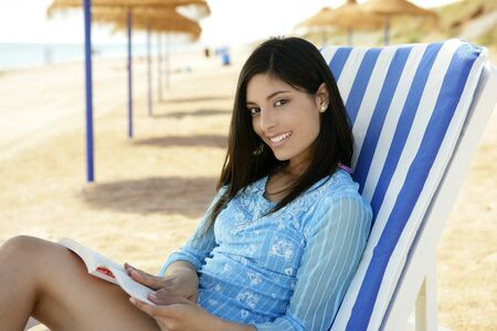 indian beauty: beautiful woman with a book relaxed on the beach, mediterranean sea