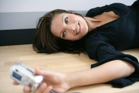 Beautiful woman taking photos herself. Black dress stripped baclground, studio shot photo
