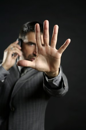 Angry businessman saying stop with hand,talking to a mobile phone photo