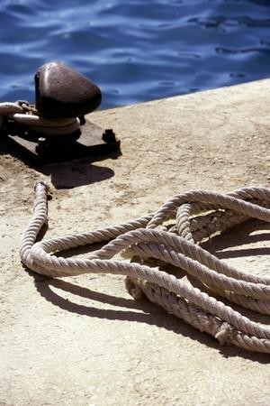 Boat bollard, ropes and knots in mediterranean harbor, macro detail photo
