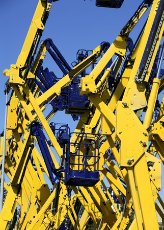 Construction crane vehicles, many elevator platform in blue and yellow colors photo