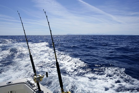 big game fishing: Fishing on the boat with trolling rod and reel. Blue Mediterranean sea. Stock Photo