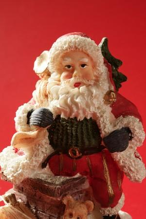 Santa Claus figurine over red background, studio shot photo