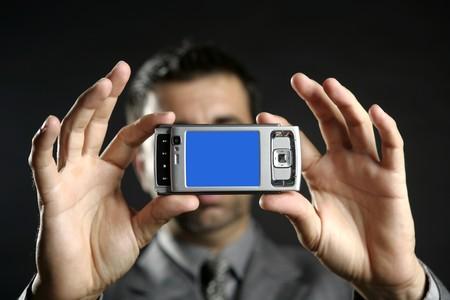 Businessman taking photos, mobile camera, black background photo