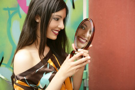 indian hair: beautiful woman making up and looking into a round mirror Stock Photo