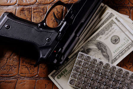 Dollar notes and gun, black pistol, mafia inspiration photo