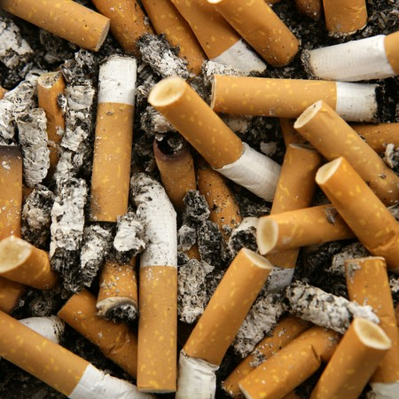 cancerous: cigarettes texture, busy ashtray square still shot