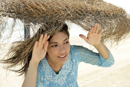 Blue dressed woman portrait, beach umbrella sunny day photo