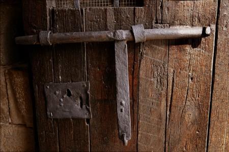 Old medieval lock on wooden castle door, real antique in Spain photo
