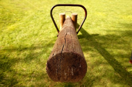 totter: old wooden balance teeter totter in the park, grass background