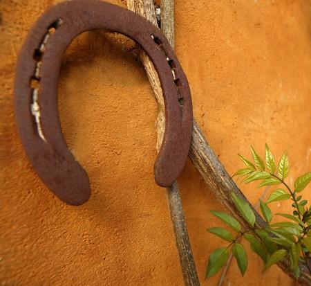 aged rusty horseshoe on the orange wall, good luck photo