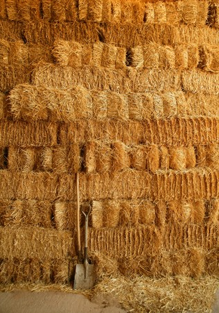 golden straw bales stacked like big wall and tools photo