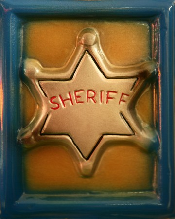 golden plastic sheriff toy star in a blue frame Stock Photo - 4186453