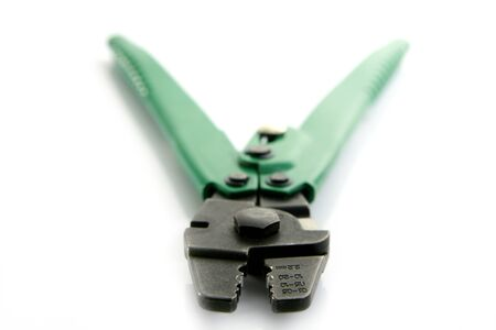 crimper: Crimper hand tool in green isolated on white, selective focus