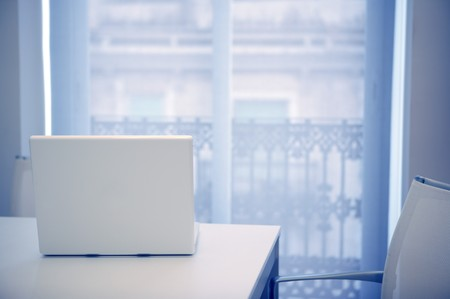 White laptop open on a white room, blue light coming from window photo