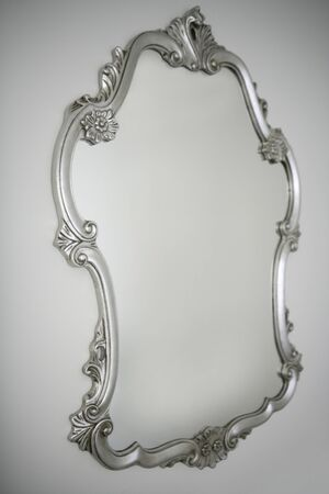 baroque silver mirror over white wall background, copy photo