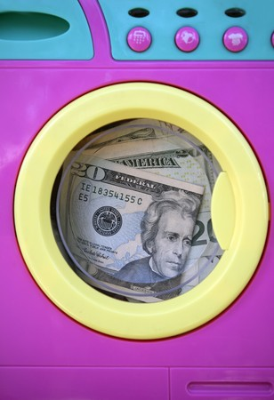 washing up: Cleaning black money dollar metaphor, laundry toy wahing machine Stock Photo
