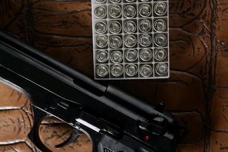 black pistol handgun with bullet box over brown leather photo
