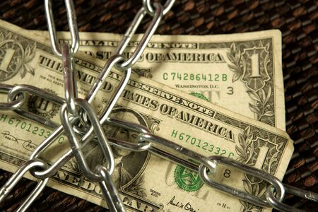 One Dollar notes in chains studio shot over brown background Stock Photo - 4238351