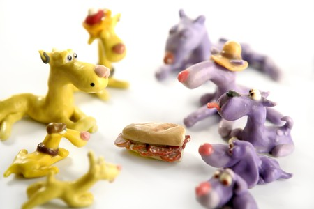 Handmade hungry plasticine dogs withy some meat to eat Stock Photo - 4238292