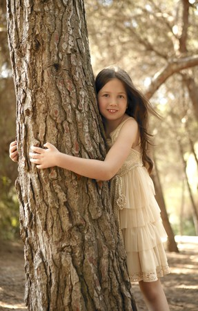 jungle girl: Teen girel hug a tree trunk in brown pine forest