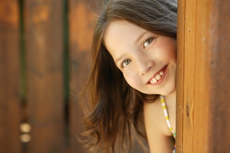 beautiful young girl portrait playing hidden behind the wooden door photo