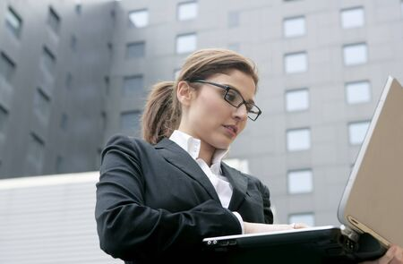 woman laptop happy: Businesswoman with laptop computer on the city, buildings on background Stock Photo