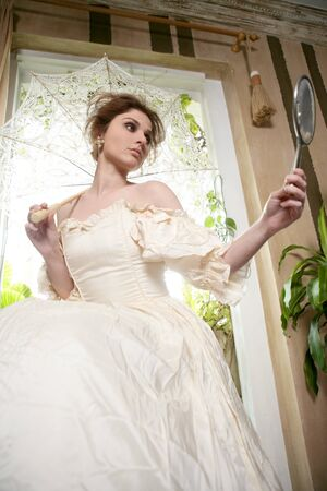 Victorian beautiful woman, white dress at home looking hand mirror