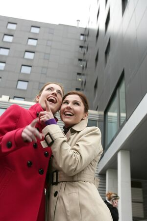 Two happy young women with winter coats, black building background photo
