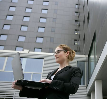 Businesswoman with laptop computer on the city, buildings on background photo