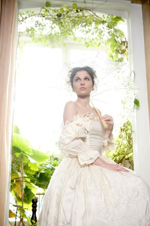 Victorian beautiful woman, white dress at home window with plants
