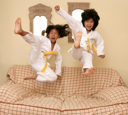 karate female: Two little asian judo dressed gils jumping over the sofa at home