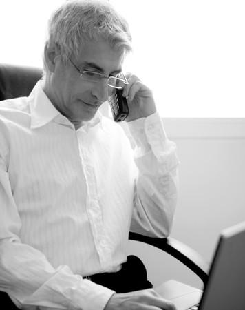 businessman working laptop computer, senior gray hair talking phone photo