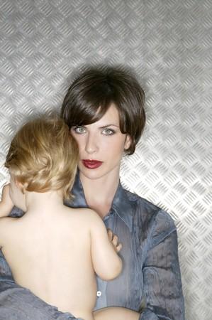 Metallic beautiful woman hug a baby over steel background photo