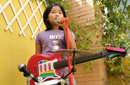 live rock concert at home one little girl singing and playing guitar Stock Photo