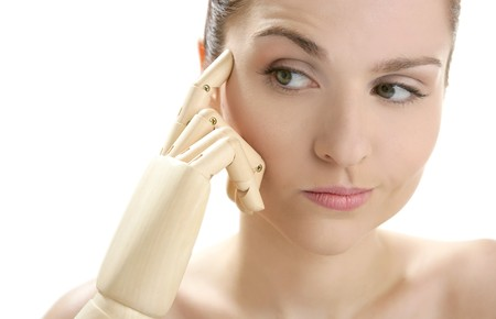Funny woman cosmetic portrait, thinking with mannequin wooden hand photo
