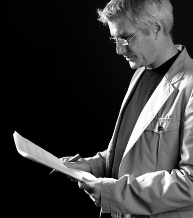 businessman reading at work, senior gray hair, isolated on black photo