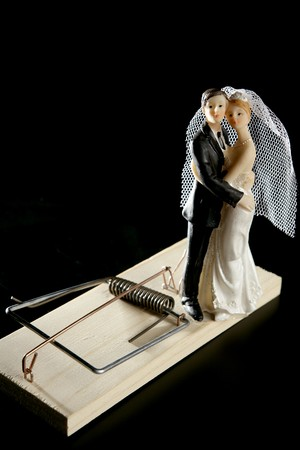 Marriage seen as a mouse trap classic male idea isolated over black photo