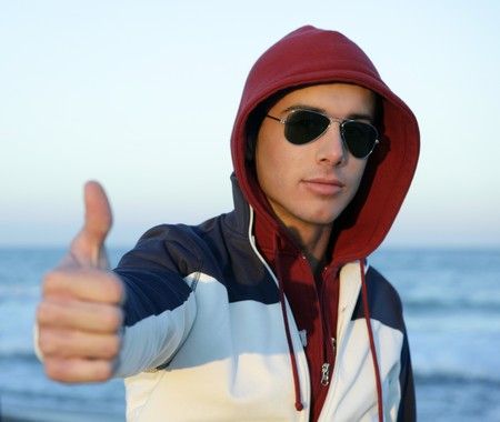 Grunge young man with hood and sunglasses at the beach Stock Photo - 4348637