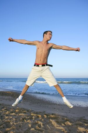 Young man jumping at the blue beach photo