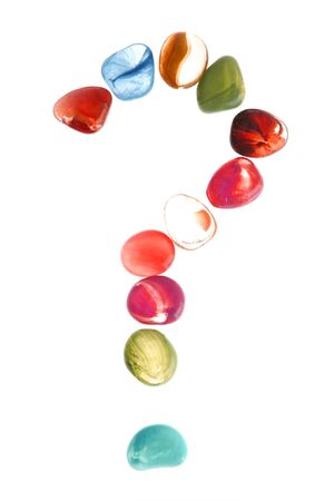 Colorful stones over white with question mark shape photo