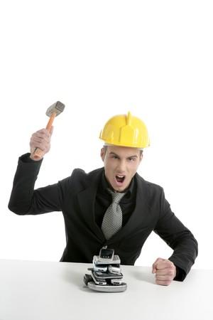 Angry businessman, hammer against telephones, yellow helmet photo