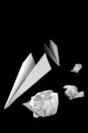 throw up: Trash paper and air plane, bored in the office metaphor, over black