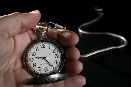 watch over: Antique vintage pocket watch on human hand over black Stock Photo