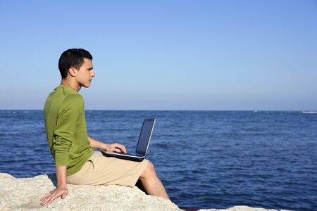 Handsome young businessman with computer on the blue ocean beach photo