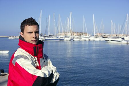 handsome boy: Handsome boy on blue marina harbor with red marine coat